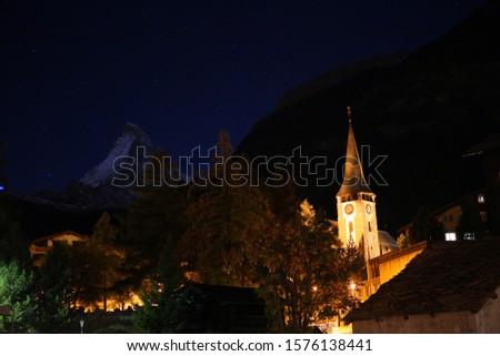 Amazing Matterhorn mountain at night with Zermatt churches and blue skies with stars. #1576138441