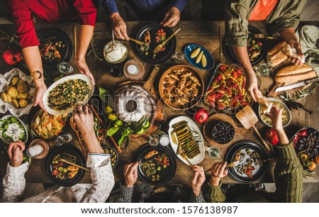 Traditional Turkish celebration dinner. Flat-lay of people feasting at table full of Turkish salads, cooked vegetables, meze starters, pastries and raki drink, top view. Middle Eastern cuisine #1576138987