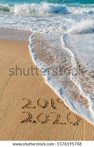 2019 2020 written in the sand with a wave erasing 2019- New Year's concept #1576195768