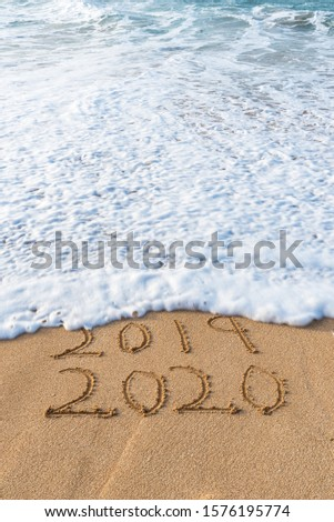 2019 2020 written in the sand with a wave erasing 2019- New Year's concept #1576195774