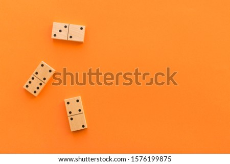 Playing dominoes on a orange table. Leisure games concept. Domino effect #1576199875