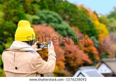 woman tourist traveler enjoy taking photo of the scenery Autumn view beside the road at Countryside, traveling in Countryside o Japan prefecture #1576238092