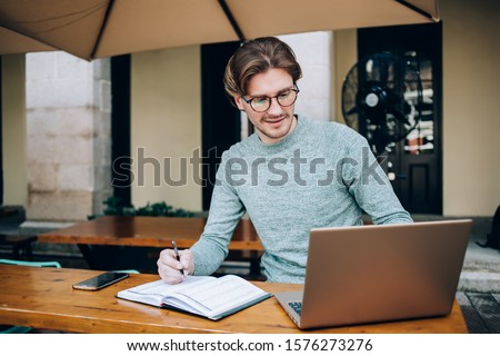 Handsome man in casual outfit and glasses writing in notebook and browsing laptop while sitting at table in yard near building #1576273276