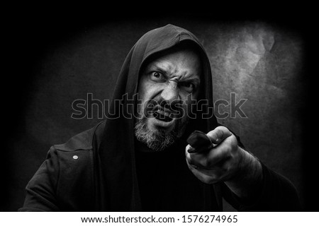 Black and white portrait of a bald bearded man in a hood on a dirty gray background. Maniac with a knife concept. #1576274965