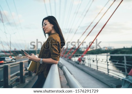 Young asian trendy dressed woman in eyewear reading news from social networks on smartphone resting on urban setting bridge, female travel blogger using mobile phone for share publications during trip #1576291729