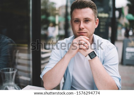 Young smart intellectual male in glasses wearing blue shirt white t shirt and wrist watches sitting at table in outdoor terrace  #1576294774