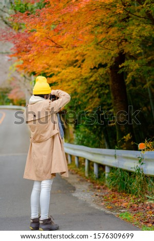 woman tourist traveler enjoy taking photo of the scenery Autumn view beside the road at Countryside, traveling in Countryside of Japan prefecture #1576309699