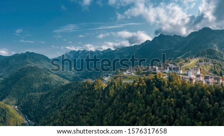 Aerial view; drone photo of hotels buildings and ski resorts of Rosa Plateau alpine mountain olympic village; beautiful summer landscape, mounts and valleys terrain; popular touristic route #1576317658