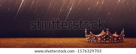 low key image of beautiful queen/king crown over gold glitter table. vintage filtered. fantasy medieval period #1576329703