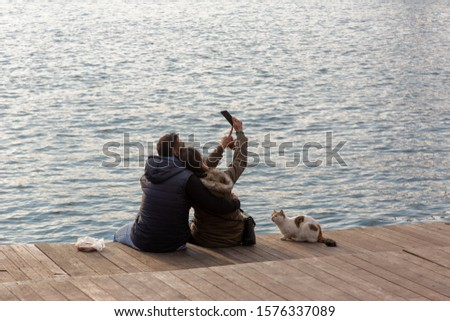 Couple take selfie picture while sitting on the boardwalk of the Karakoy shoreline and a cat watch them curiously.