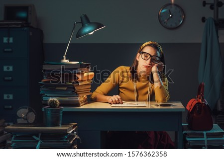 Sad bored woman working overtime, she is sitting at desk late at night and leaning on her arm #1576362358