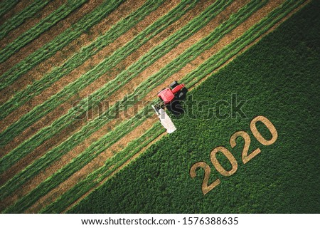 2020 Happy Ney Wear concept and red tractor mowing green field. #1576388635