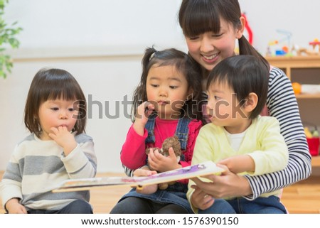 Childcare teacher reads picture books to children