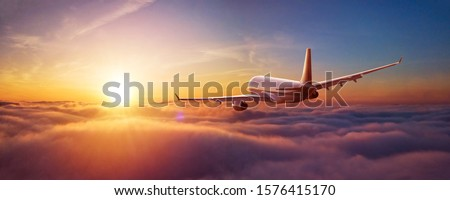 Passengers commercial airplane flying above clouds in sunset light. Concept of fast travel, holidays and business. #1576415170