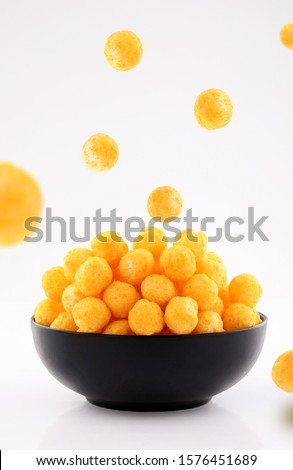 puffed ball cheese corn chips in black bowl and sprinkled isolated on white background #1576451689
