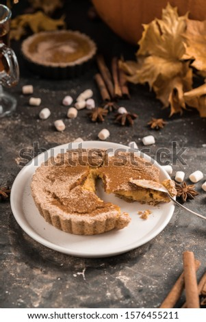 pumpkin homemade vegan pie and spices cinnamon, anis, orange  pumpkins with yelllow dry autumn leaves decor on dark table background.Harvesting,autumn and Thanksgiving concept #1576455211