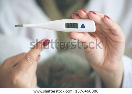 Flu sick woman is showing a thermometer with a high body temperature. #1576468888