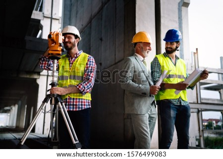 Team of construction engineers, architects working on building site #1576499083