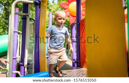 Little child boy playing on playground in the city park #1576511050