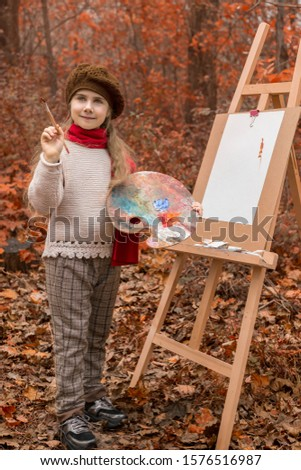 Beautiful girl artist with paints and palette, paints a picture on an easel in the autumn forest. Creative work in nature and fresh air. Useful creativity and relaxation for children.