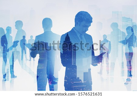 Young businessman with smartphone and his colleagues standing together in modern city. Concept of teamwork and business partnership. Toned image #1576521631