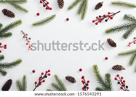 Christmas minimal concept - christmas composition made of evergreen tree branch, pinecone and red berries. Frame composition with copy space. Flat lay, top view. Holiday decoration. Abstract template. Royalty-Free Stock Photo #1576543291