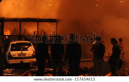 RIO DE JANEIRO, BRAZIL - OCTOBER 08: Black Bloc protesters look at a burned bus during schoolteachers demonstrations demanding better wages on October 8th, 2013 in Rio de Janeiro, Brazil. #157654613