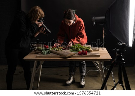 two photographers making food composition for commercial photography and taking photo on digital camera