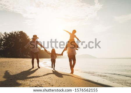Happy family travel on beach in holiday,Summer vacations. Happy family are having fun on a tropical beach in sunset. Father and mother and children playing together outdoor on beach. #1576562155