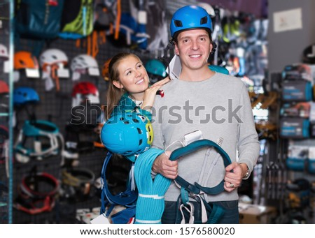 Young positive couple standing with sports equipment in sports store  #1576580020