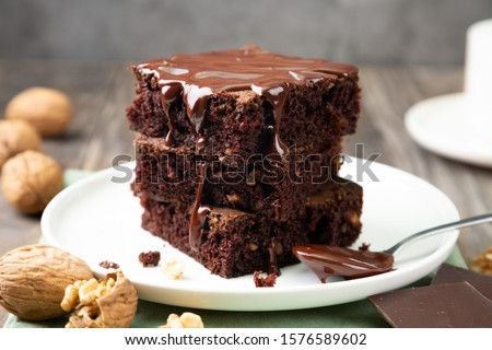 Chocolate spongy brownie cakes with walnuts and melted chocolate topping on a stack  #1576589602