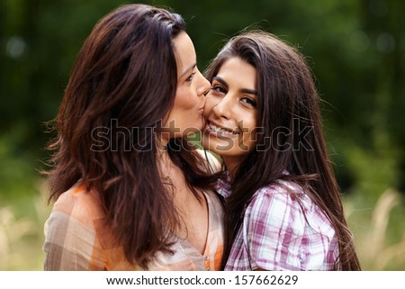 Closeup of mother kissing her daughter on the cheek