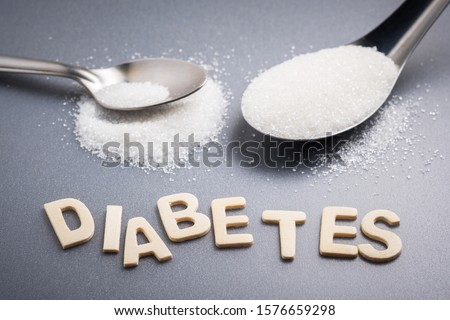 Diabetes text with tablespoon and teaspoon of white sugar, amount of sugar necessary concept #1576659298
