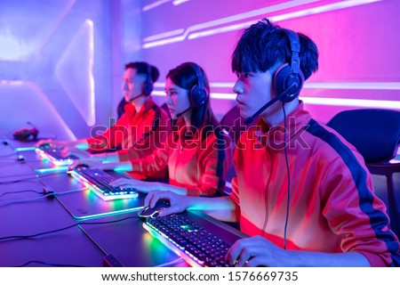 Team of asian teenage cyber sport gamers play in multiplayer PC video game on eSport tournament #1576669735