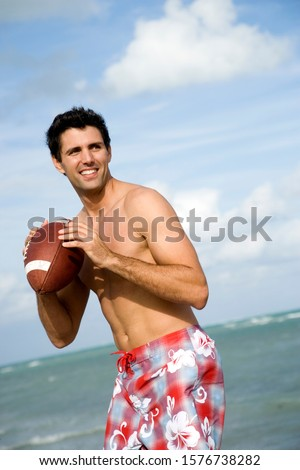 A young man with a ball on the beach #1576738282