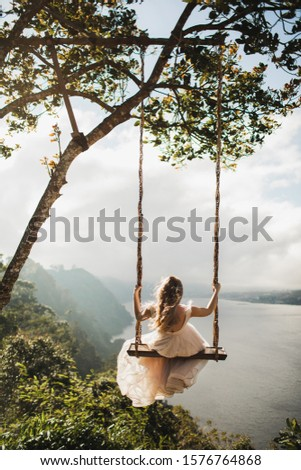 Woman swinging outdoors over amazing mountain, jungle and lake view over a cliff in Bali Wanagiri hidden hill. Freedom and wanderlust concept. Popular balinese tourist landmark and photo point.