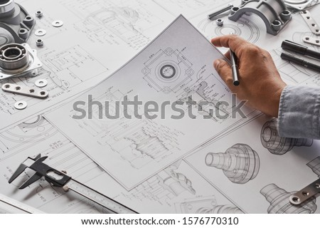 Engineer technician designing drawings mechanical parts engineering Engine manufacturing factory Industry Industrial work project blueprints measuring bearings caliper tools #1576770310