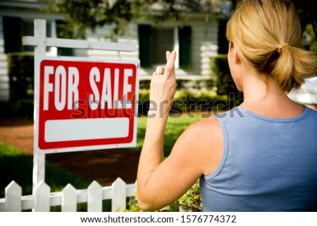 Woman standing by a for sale sign outside a family house, fingers crossed #1576774372