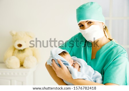 A medical practitioner holding a newborn baby #1576782418