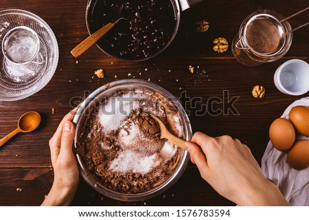 Top view female hands mix cocoa powder, sugar and flour to make dough with melted chocolate and walnuts for delicious homemade brownie cake. #1576783594