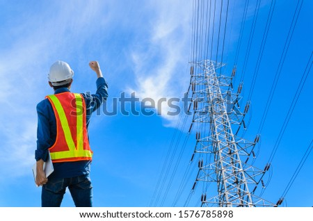 Successful engineers stand against high voltage poles on a blue background. #1576785898