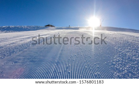 A skier going down the slope in Goldeck, Austria. Perfectly groomed slopes. The crispy snow is thrown up under the pressure of the ski. Man wears green trousers, blue jacket and helm for protection #1576801183