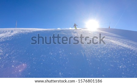 A skier going down the slope in Goldeck, Austria. Perfectly groomed slopes. The crispy snow is thrown up under the pressure of the ski. Man wears green trousers, blue jacket and helm for protection #1576801186