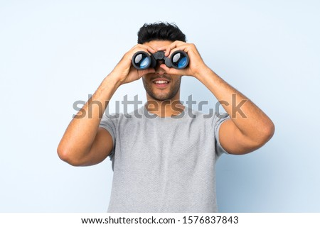 Young handsome man over isolated background with black binoculars Royalty-Free Stock Photo #1576837843