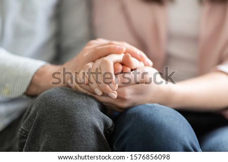 Close up of man and woman holding hands, giving psychological support #1576856098