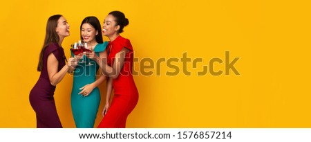 Three Diverse Girls Having Fun On A Party Holding Red Wine Glasses Talking And Laughing Over Yellow Studio Background. Panorama #1576857214