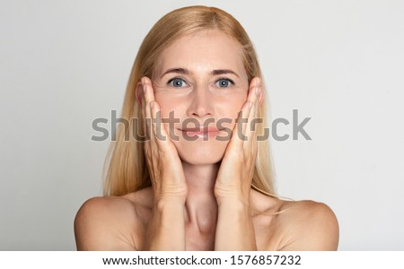 Anti aging treatment. Middle-aged woman touching cheeks over grey studio background #1576857232