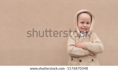 Little boy 3-5 years old, autumn beige wall, in warm casual clothes, sweater with hood, happy smiling, free space for copy text. Christmas mood of happiness fun and relaxation. Holiday concept #1576870348