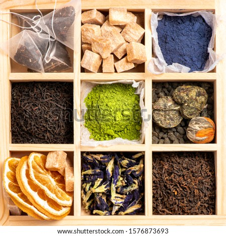 Different types of tea in a wooden box, top view. Black tea, puer, blue and green matcha tea, green tea and cane sugar. #1576873693