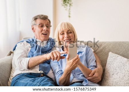 Happy senior spouses surfing internet on cellphone and watching photos, free space #1576875349
